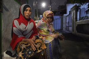 Somalian refugees Stahil and Safiya sit in a Jakarta street at night.
