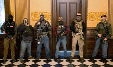 A militia group, including Pete Musico, right, who was charged over a plot to kidnap the Michigan governor, attack the state capitol building and incite violence, stands in front of the governors office after protesters occupied the state capitol building in Lansing, Michigan, on 30 April 2020.