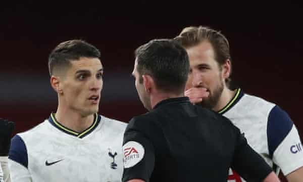 Erik Lamela protests to Michael Oliver after being shown the red card while Harry Kane covers his mouth to prevent lipreading as he talks to the referee