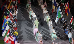 Flag bearers and volunteers enter the Olympic Stadium during the closing ceremony
