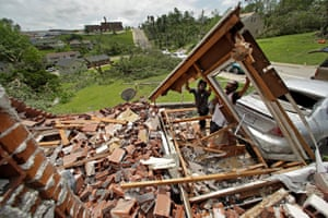 Tavaris McClain and Tyree Thompson clear debris to free McClain's mother's car outside her destroyed home on 23 May 2019 after a tornado tore though Jefferson City, Missouri