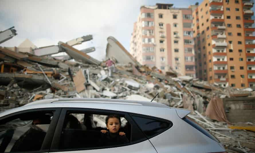 Child looks out of car window surrounded by destroyed buildings.