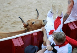 Pamplona, Spain: A reveller is tossed by a bull