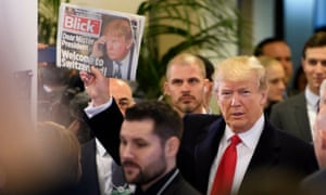 Donald Trump holds up Swiss newspaper Blick as he arrives at the Congress Centre in Davos on Friday.