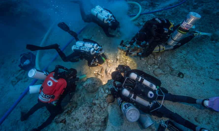 The team examining the bone find. The bones likely survived because the ship sank fast into the cool depths and was buried by a mound of silt that slid down the cliff after the vessel.