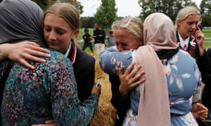 High school students from a Christian school embrace Muslims waiting for news of their relatives at a community centre, following Friday's shooting in Christchurch.