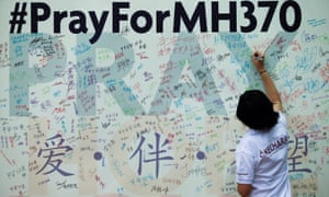 A woman writes a message on a board in Kuala Lumpur soon after the plane's disappearance