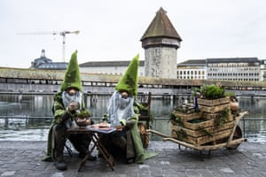 Lucerne, Switzerland. Costumed participants pose in front of the Chapell Bridge on the opening day of a carnival