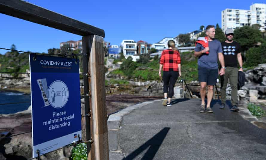 A social distancing sign sits on the fence along the walking path from Bondi to Bronte.