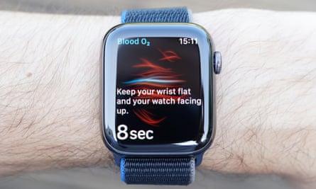 Фотография, показывающая показания измерений насыщения крови кислородом с новых Apple Watch. Для получения надежных показаний вам необходимо неподвижно положить руку на стол в течение 15 секунд.