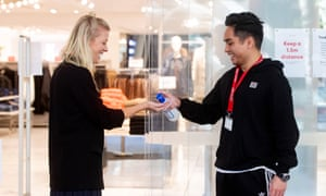 An employee of an H&M store in Sydney makes sure Covid-19 guidelines are followed with the use of hand sanitiser. Should I wear a mask or use public transport as restrictions are lifted in Australia?