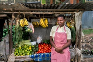 A member of the Nairobi Young and Old cooperative stands in front of her fruit and vegetable stall in a local market in Nairobi, Kenya