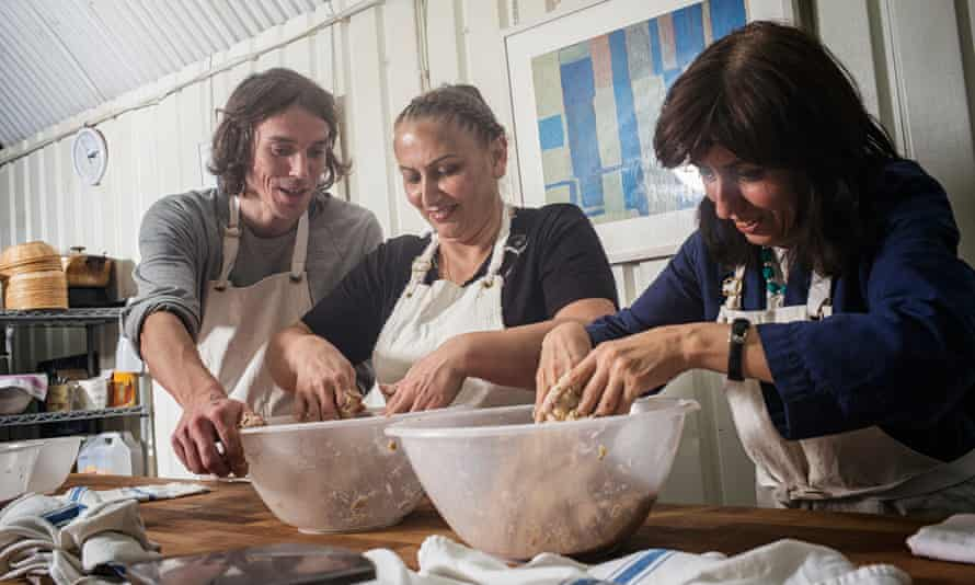 Sarah (not her real name), centre, and Tahmineh Gashtasebi being taught baking skills by Jean Kern, left, at the E5 Bakehouse in London Fields