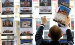 An estate agent replaces a sold listing in the shop window