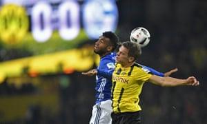 Schalke's Eric Maxim Choupo-Moting, left, and Dortmund's Matthias Ginter challenge for the ball