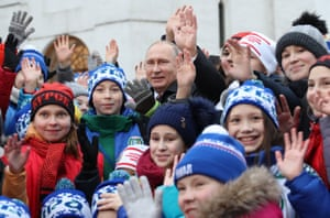 Vladimir Putin poses for a photo with children before a Christmas show at the State Kremlin Palace in Moscow