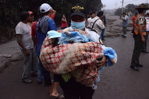 A police officer carries a baby in El Rodeo village