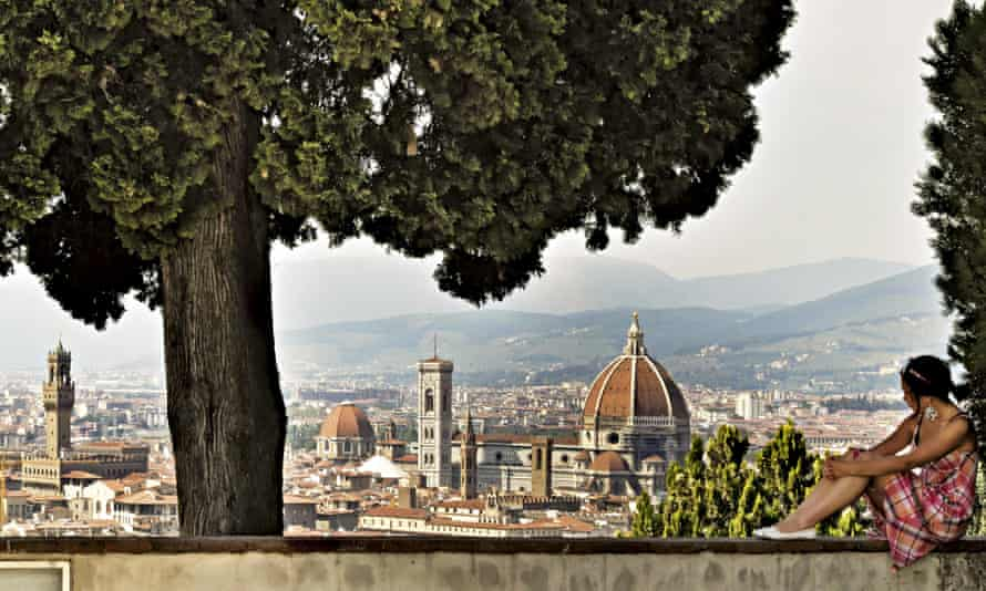 A woman looks out across the Florence skyline from Monte alle Croci