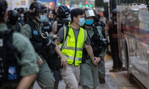 A man is detained by police during a silent march against the national security law in Hong Kong