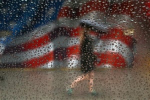 A woman walks with an umbrella in the rain past a US flag painted on a building in Manhattan