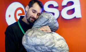 ESA staff member Mattial Malmer rests his head against a model of comet 67P/ Churyumov-Gerasimenko, target for the Rosetta mission, which ended today.