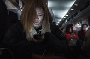 A woman reads her mobile phone on a crowded train between Beijing and Shijiazhuang