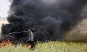 A Palestinian slings stones towards Israeli soldiers during clashes along the border with Israel.