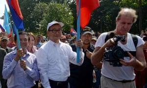 Australian film-maker James Ricketson (right) filming as opposition leaders Sam Rainsy (centre) and Kem Sokha (left) attend a demonstration in Phnom Penh in 2013.