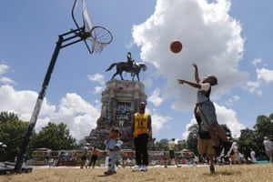 Richmond, Virginia, US: Isaiah Bowen takes a shot at a basketball hoop as his father, Garth, looks on in front of the statue of Confederate general Robert E Lee on Monument Avenue