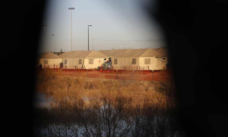 Tents are seen through a hole in the tarp that covers the fence of the Tornillo detention camp, in December.