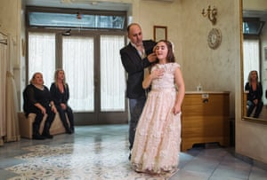In the designer's atelier, Francesca tries on her dress for last-minute adjustments, as her mother and grandmother look on