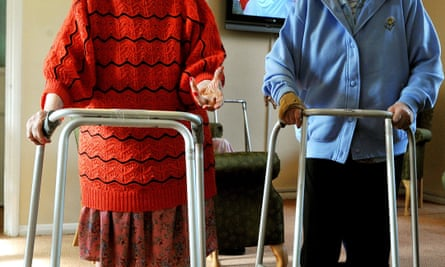 Two elderly people using walking frames