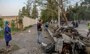 Residents clean a street after it was hit by a missile in Gandja, near the disputed Nagorno-Karabakh province's capital, Stepanakert.