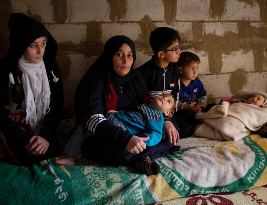 Farzad Uaz holds her two year old son, Moaz who has spina bifida, accompanied by her other four children in the unfinished apartment they are renting in Zahlé, Lebanon, 23 March 2021.