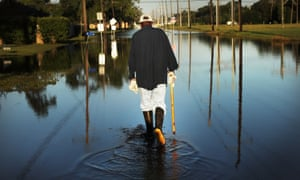 Paul Morris checks on neighbours' homes in a flooded district of Orange as Texas slowly moves toward recovery from the devastation of Hurricane Harvey.