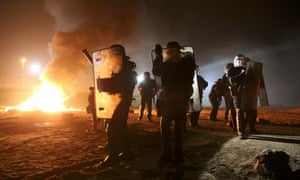 French riot police secure an area as flames are seen on the eve of the evacuation