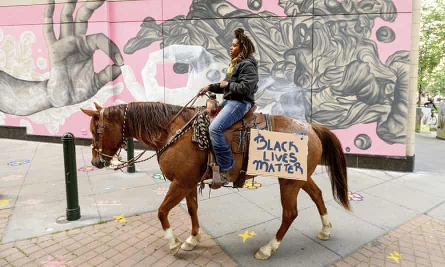 Brianna Noble rides her horse Dapper Dan through downtown Oakland last Friday.