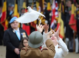 People release a dove during a commemoration ceremony at the tomb of the unknown soldier at the Congress Column