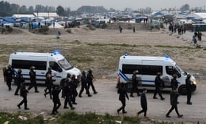 French police walk along the edge of the Calais refugee camp