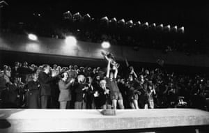 Liverpool captain Phil Thompson hoists the trophy high as the players celebrate