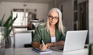 Senior stylish woman taking notes in notebook while using laptop at home.