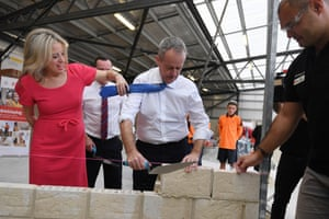 Bill Shorten's wife, Chloe, moves his tie as he lays a brick during a visit to a Tafe campus in Perth