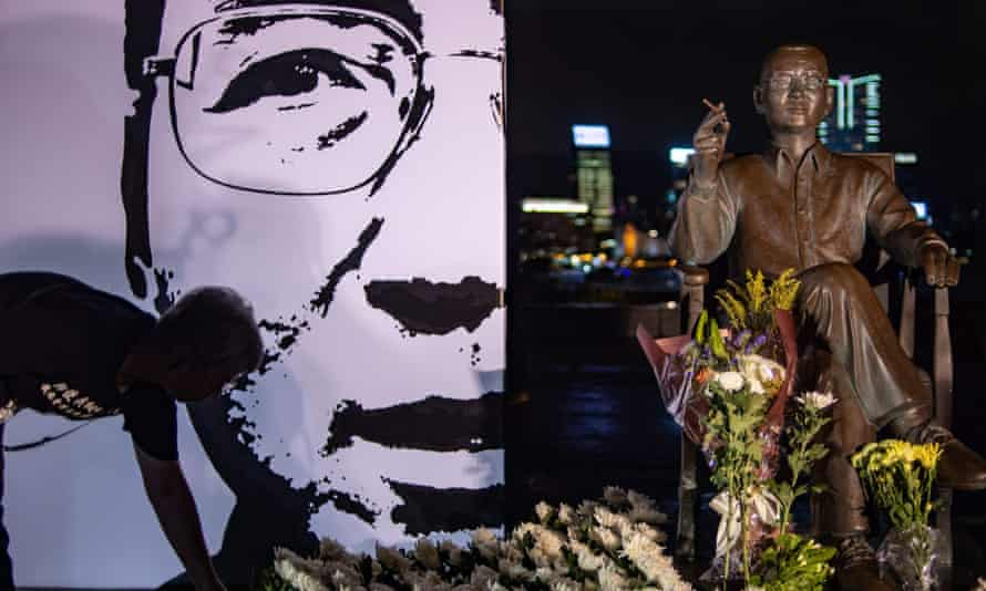 People lay white flowers in front of the statue of late Chinese Nobel dissident Liu Xiaobo at a memorial event on his death anniversary outside Tamar Park in Hong Kong
