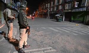 Indian paramilitary troopers stand guard at a roadblock in Srinagar, Kashmir.