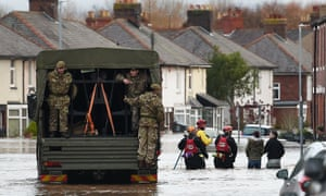 Members of the British army assist the emergency services in a flooded street in Carlisle.