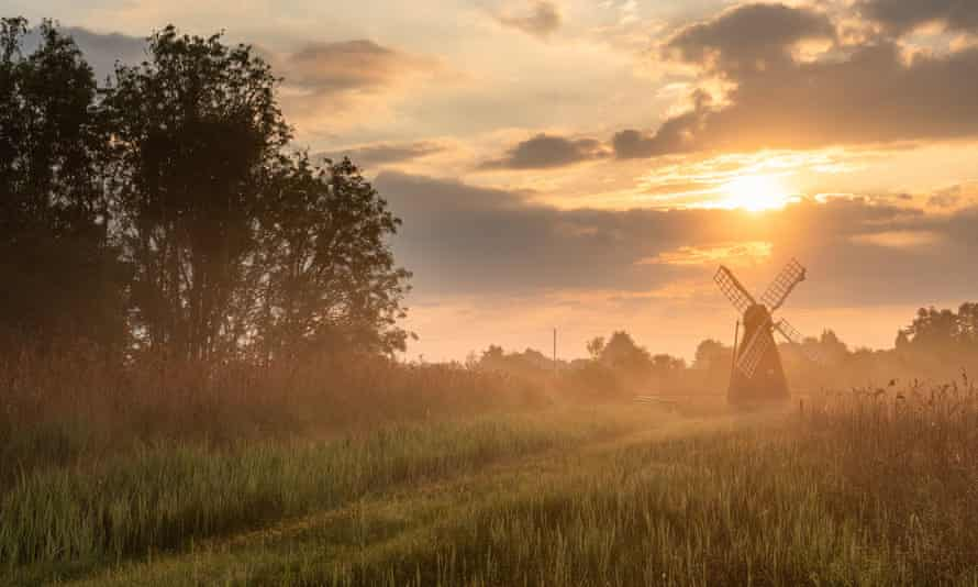 The sun rising behind the wind pump at Wicken Fen National Nature Reserve