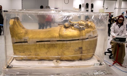 An archeologist works next to the gilded coffin of King Tutankhamun, which is undergoing restoration at the Grand Egyptian Museum in Giza, Egypt.