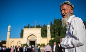 Muslim man stands in front of mosque in Xinjiang