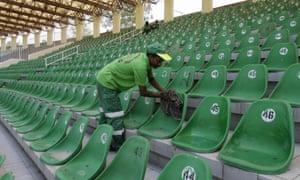 A worker cleans seats at Gaddafi stadium.