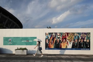 A woman walks past a billboard promoting the Rugby World Cup at the International Stadium Yokohama.